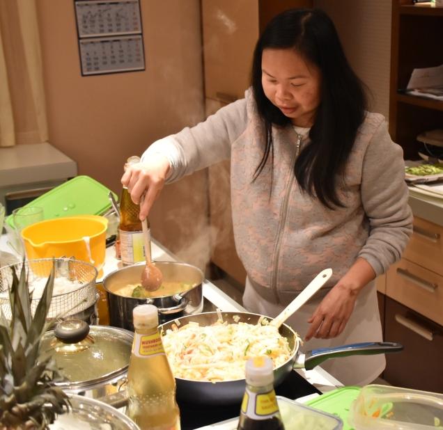 Jaj kuha riževe rezance s škampi, s pikantno zelenjavo in sesekljanimi slanimi arašidi, ki so zelo po slovenskem okusu